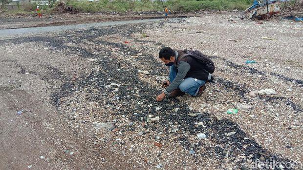 Warga mengambil batu bara yang berhamburan di Pantai Sekembu, Jepara, Selasa (21/1/2021)