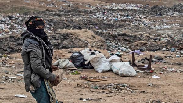 Wanita berjilbab mencari mencari sesuatu di tumpukan sampah. Warga lainnya menemukan sepatu bot kecil. (Delil Souleiman/AFP)