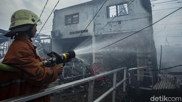 Petugas pemadam kebakaran Jakarta Pusat melakukan pendinginan di Jalan Citarum Jati Baru, Jakarta, Jumat (22/1/2021).