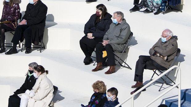 Gaya Senator Vermont, Bernie Sanders, yang memakai jaket musim dingin dan sarung tangan bermotif menjadi viral di media sosial. (AP/Carolyn Kaster)