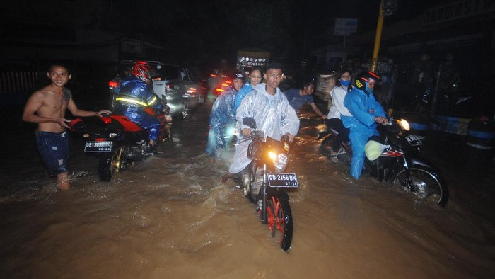 Warga menerobos banjir di salah satu ruas jalan di Kota Manado, Sulawesi Utara, Jumat (22/1/2021). Curah hujan dengan intensitas tinggi selama sekitar tiga jam mengakibatkan sejumlah daerah tergenang air. ANTARA FOTO/Adwit B Pramono/hp.