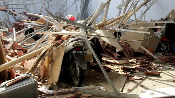 Warga memotret atap rumah yang ambruk akibat gempa bumi di Mamuju, Sulawesi Barat, Kamis (14/1/2021). BMKG Sulawesi Barat mencatat gempa bumi berkekuatan 5,9 skala richter terjadi pada pukul 14:35:49 WITA di empat kilometer Barat Laut Majene-Sulbar dengan kedalaman 10 Km dan tidak berpotensi tsunami. ANTARA FOTO/Akbar Tado/wsj.