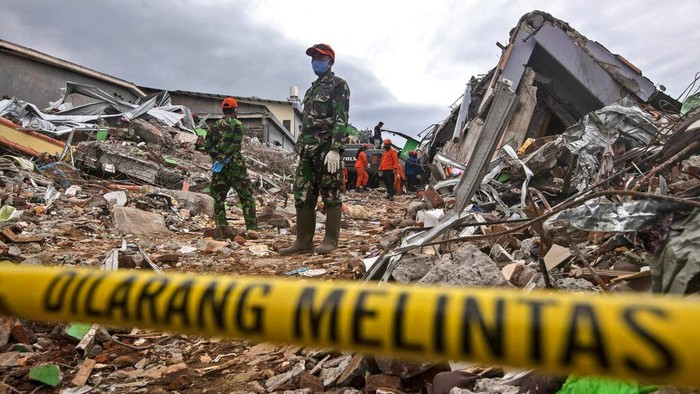 Rescuers search for victims at the ruin of a building flattened during an earthquake in Mamuju, West Sulawesi, Indonesia, Saturday, Jan. 16, 2021. Damaged roads and bridges, power blackouts and lack of heavy equipment on Saturday hampered Indonesias rescuers after a strong and shallow earthquake left a number of people dead and injured on Sulawesi island. (AP Photo/Yusuf Wahil)