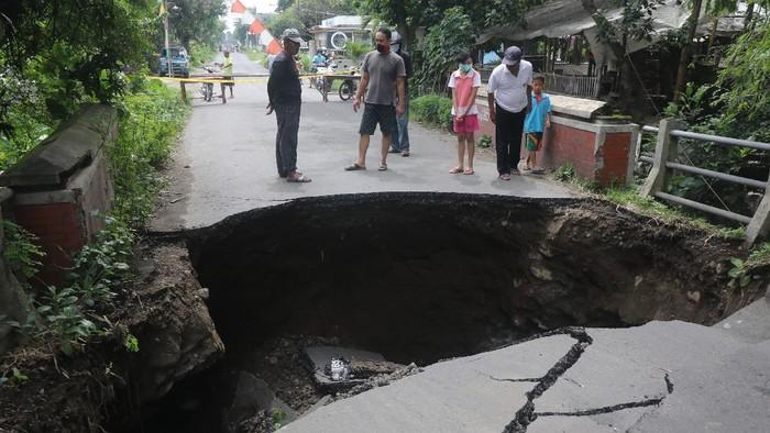 Warga mengamati jembatan rusak di Desa Gedangsewu, Kediri, Jawa Timur, Sabtu (23/1/2021). Jembatan yang menjadi akses utama antarkecamatan di wilayah tersebut ambrol karena tergerus derasnya aliran sungai Bening usai hujan deras. ANTARA FOTO/Prasetia Fauzani/aww.