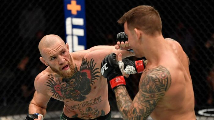 ABU DHABI, UNITED ARAB EMIRATES - JANUARY 23: In this handout image provided by the UFC, (L-R) Conor McGregor of Ireland punches Dustin Poirier in a lightweight fight during the UFC 257 event inside Etihad Arena on UFC Fight Island on January 23, 2021 in Abu Dhabi, United Arab Emirates. (Photo by Jeff Bottari/Zuffa LLC via Getty Images)