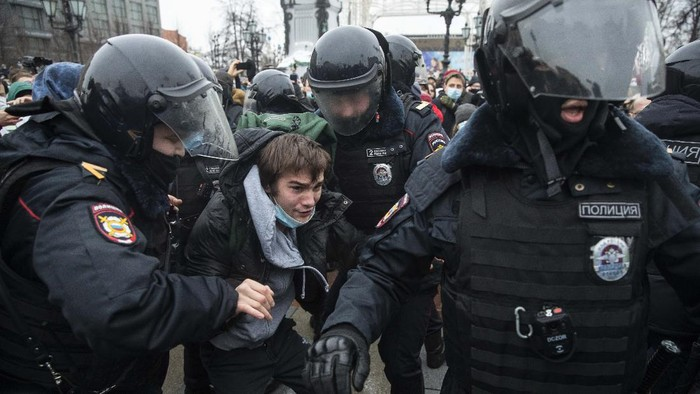 Police officers detain a man dressed in a horned, fur hat, and holding Russian flag during a protest against the jailing of opposition leader Alexei Navalny in Moscow, Russia, Saturday, Jan. 23, 2021. Russian police on Saturday arrested hundreds of protesters who took to the streets in temperatures as low as minus-50 C (minus-58 F) to demand the release of Alexei Navalny, the countrys top opposition figure. (AP Photo/Pavel Golovkin)