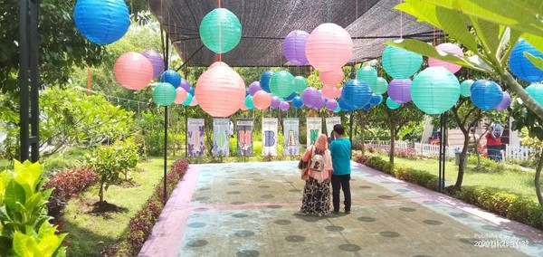 Liat tuh guys, keluarga itu sedang mengabadikan momen dibawah balon-balon yang indah
