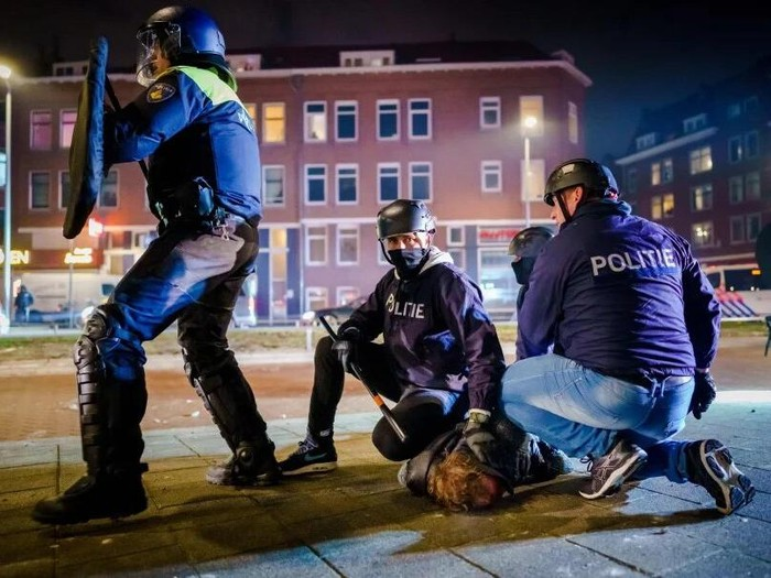 Dutch policemen arrest a man during clashes with a large group of young people on Beijerlandselaan in Rotterdam, on January 25, 2021. - The Netherlands was hit by a second wave of riots on January 25 evening after protesters again went on the rampage in several cities following the introduction of a coronavirus curfew over the weekend. Riot police clashed with groups of protesters in the port city of Rotterdam, where they used a water canon. (Photo by Marco de Swart / ANP / AFP)