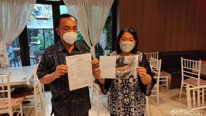 Erni Marsaulina (50) dan Raplan Sianturi (59) menunjukkan surat aduan ke Polda Jateng dan foto putra mereka yang meninggal di ruang isolasi, Rabu (27/1/2021).