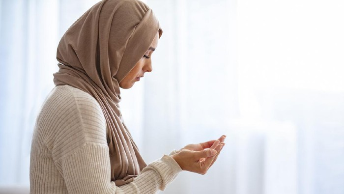 Young Woman Praying. Young Muslim woman praying, indoors. Young Muslim woman in beige hijab and traditional clothes praying for Allah, copy space. Arab Muslim woman praying