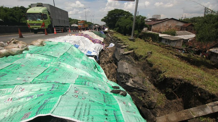 Petugas memeriksa jalan tol yang ambles di ruas tol Surabaya-Gempol KM 06+200, di Surabaya, Jawa Timur, Rabu (27/1/2021). Jalan tol ambles yang terjadi pada  Selasa (26/1) yang sebelumnya ditemukan retakan pada Senin (25/1) di lokasi tersebut mengakibatkan kemacetan lalu lintas yang sangat panjang. ANTARA FOTO/Didik Suhartono/hp.