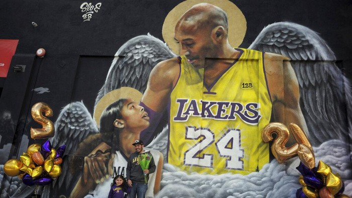 Jose Jara with his three-year-old daughter Giana poses for a picture in front of a mural on the side of Hardcore Fitness along Pico Blvd as fans of Kobe Bryant celebrate the life and legacy around murals and makeshift memorials in Los Angeles on Tuesday, Jan. 26, 2021. (Keith Birmingham/The Orange County Register via AP)