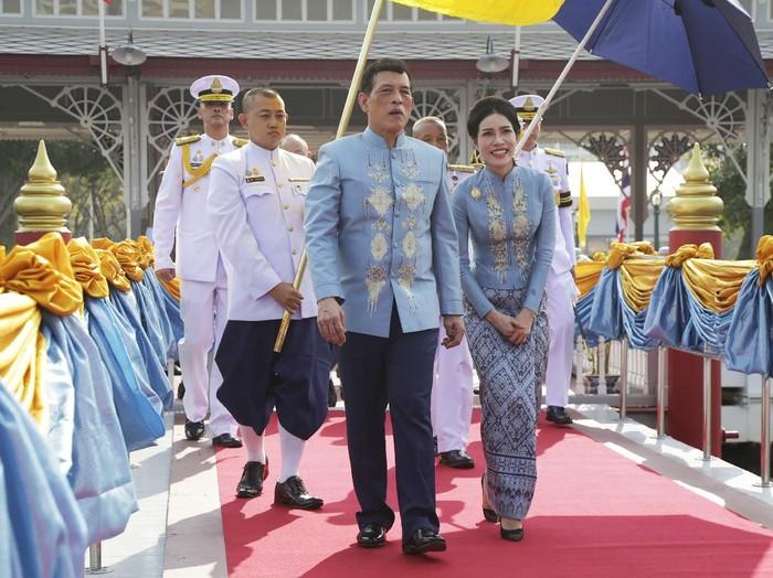 Thai King Maha Vajiralongkorn, center, and his royal noble consort Sineenat Wongvajirabhakdi, right, arrive at the Wasukri pier during a merit-making ceremony for her 36th birthday in Bangkok, Thailand, on Tuesday, Jan. 26, 2021. Thai royal noble consort Sineenat was born on Jan. 26, 1985 .(AP Photo)