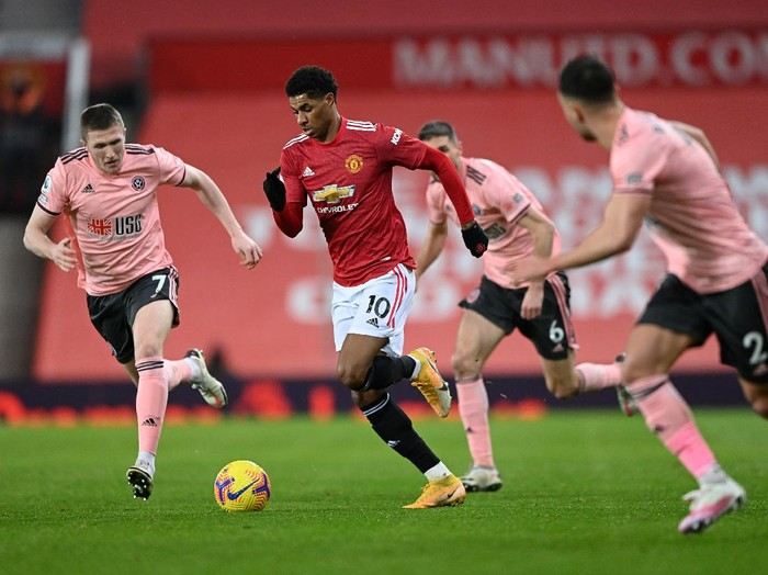 MANCHESTER, ENGLAND - JANUARY 27: Marcus Rashford of Manchester United is chased by John Lundstram of Sheffield United  during the Premier League match between Manchester United and Sheffield United at Old Trafford on January 27, 2021 in Manchester, England. Sporting stadiums around the UK remain under strict restrictions due to the Coronavirus Pandemic as Government social distancing laws prohibit fans inside venues resulting in games being played behind closed doors. (Photo by Laurence Griffiths/Getty Images)