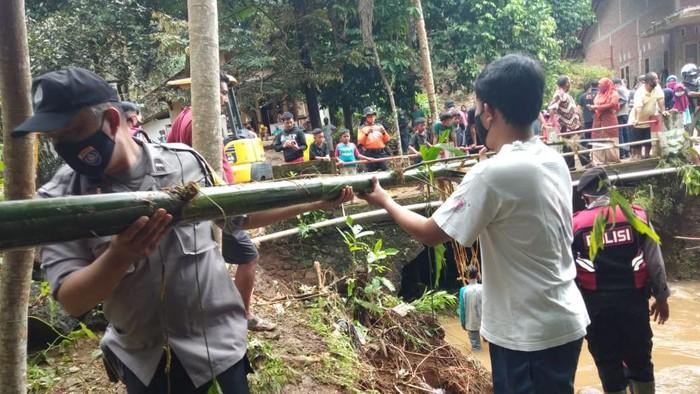 Polisi dan warga bergotong royong membersihkan bambu yang menyumbat Sungai Kaliparuk, Banyumas. Akibat meluapnya sungai ini viral disebut banjir bandang Banyumas.