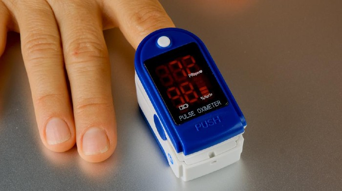 Woman hand introduced in a oximeter to check oxygen levels and pulse because Covid-19 pandemic