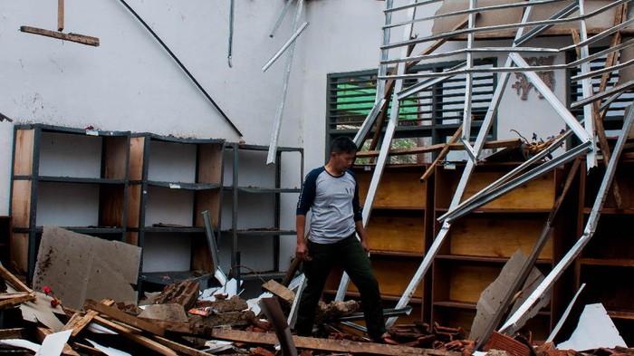 Seorang guru melihat kondisi di sekitar atap bangunan sekolah yang ambruk di SMAN 12 Pandeglang, Banten, Kamis (28/1/2021). Menurut pihak sekolah dua atap ruang biologi dan perpustakaan tersebut ambruk akibat angin kencang disertai hujan deras pada Rabu (27/1/2021) dan menyebabkan kerugian hingga Rp100 juta. ANTARA FOTO/Muhammad Bagus Khoirunas/hp.