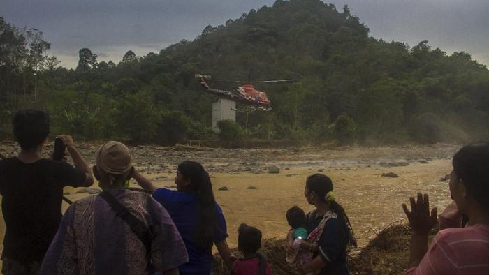 Sejumlah warga membawa logistik bantuan banjir bandang di Desa Datar Ajab, Kabupaten Hulu Sungai Tengah, Kalimantan Selatan, Minggu (24/1/2021). Bantuan berupa tenda, sembako serta perlatan dapur dari TNI Angkatan Udara Lanud Sjamsudin Noor, Dharma Pertiwi Peduli, Kepala Staf Angkatan Udara dan Badan Penanggulangan Bencana Daerah (BPBD) Provinsi Kalsel itu didistribusikan melalui jalur udara ke wilayah pedalaman pegunungan Meratus. ANTARA FOTO/ Bayu Pratama S/foc.