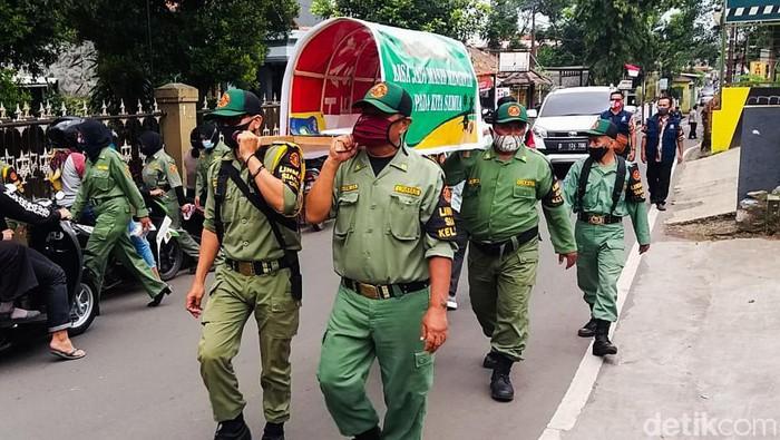 Sosialisasi bahaya COVID-19 masih terus dilakukan di Cimahi, Jabar. Petugas Linmas di Cimahi pun menggotong replika keranda mayat untuk ingatkan bahaya COVID-19