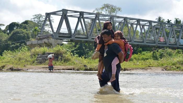 Murid sekolah menumpang kendaraan warga saat menyeberangi sungai di wilayah pedalaman desa Panca, Kecamatan Lembah Seulawah, Kabupaten Aceh Besar, Aceh, Jumat, (22/1/2021). Menurut aparat desa, sejak tahun 2004 pascaputusnya jembatan gantung dan kemudian tahun 2008 dibangun jembatan kontruksi beton rangka baja yang hingga saat ini tidak tuntas pembangunannya, anak sekolah dan warga terpaksa menyeberangi sungai dan jika musim penghujan air sungai deras aktivitas belejar lumpuh dan begitu juga pemasaran komoditas pertanian ke ibukota provinsi Aceh terhenti karena tidak ada jalan alternatif lainnya. ANTARA FOTO/Ampelsa/hp.