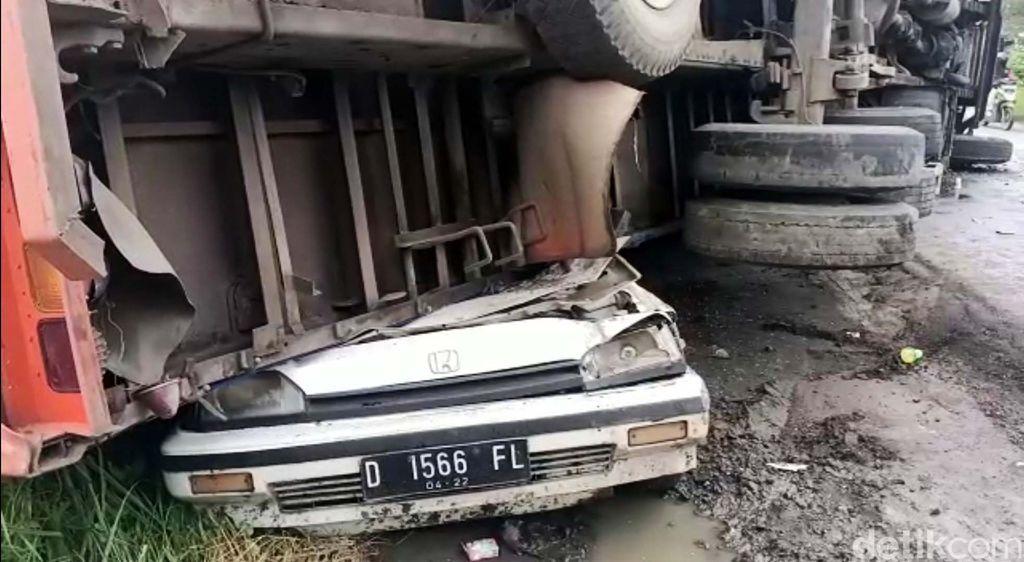 Truk pengangkut air minuman dalam kemasan terguling menimpa mobil di Jalan Raya Bogor - Sukabumi. Mobil yang tengah diparkir itu pun ringsek.