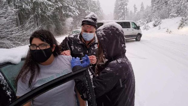 This photo provided by Josephine County, Ore., Public Health shows Josephine County Sheriff's Deputy Nicole Letona, left, receiving a COVID-19 vaccine administered by Dr. David Candelaria, center, and Leah Swanson, right, Josephine County Emergency Preparedness Coordinator, on Highway 199 near Hayes Hill, Ore., Thursday, Jan. 28, 2021, near Grants Pass. Oregon health workers who got stuck in the snowstorm on their way back from a COVID-19 vaccination event went car to car injecting stranded drivers before several of the doses expired. (Josephine County Public Health via AP)