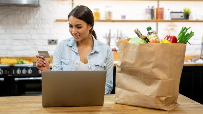 Happy woman at home buying groceries online on her laptop computer and paying by credit card