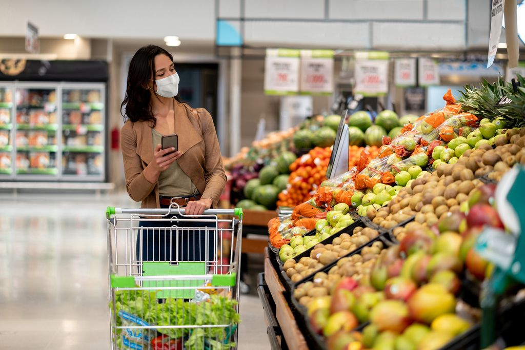 Woman shopping at the grocery store wearing a facemask to avoid the coronavirus while following a list on her cell phone - COVID-19 lifestyle concepts