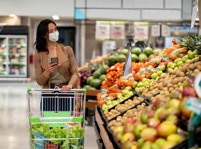 Woman wearing protective mask preparing for virus pandemic spread quarantine.Hygiene, cleaning and disinfection products.Preventive measures and protection.Supply shopping during the epidemic.