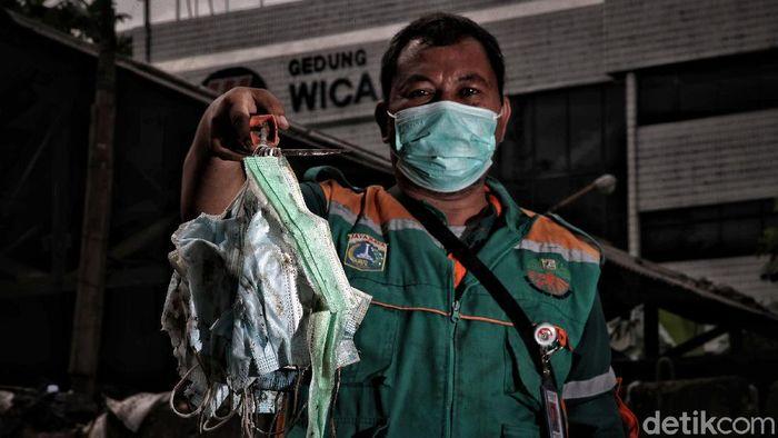 Petugas Suku Dinas Lingkungan Hidup mengambil limbah medis berupa masker di kawasan Dipo Ancol, Jakarta Utara, Senin (1/2). Dinas Lingkungan Hidup DKI Jakarta mengumumkan data limbah medis infeksius selama pandemi COVID-19 pada 2020. Berdasarkan data mereka, berat limbah medis ini yakni menembus 12.785 ton.