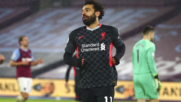 Liverpool's Mohamed Salah celebrates after scoring his side's second goal during the English Premier League match between West Ham and Liverpool at the the London Stadium in London, Sunday, Jan. 31, 2021. (Clive Rose/Pool via AP)