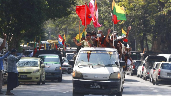 Buddhist religious and military flags are waved by supporters including Buddhist monks onboard a vehicle Monday, Feb. 1, 2021, in Yangon, Myanmar. Myanmars military has announced it will hold a new election at the end of a one-year state of emergency it declared Monday when it seized control of the country and reportedly detained leader Aung San Suu Kyi.