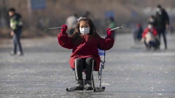 Seorang gadis berseluncur menggunakan kursi di permukaan kanal yang membeku di Beijing, China.