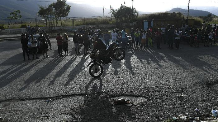 "Motorcycle stuntman Pedro Aldana performs a wheelie on his motorbike as he rides to an exhibition along the old highway from Caracas to La Guaira, Venezuela, Sunday, Jan. 10, 2021. Aldana, who prefers his show name ""Crazy Pedro,"