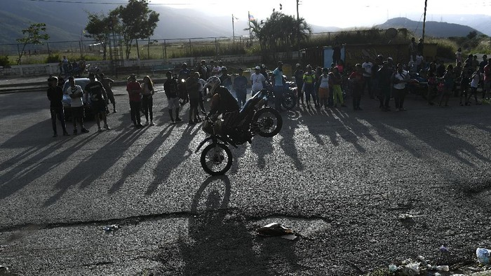 """Motorcycle stuntman Pedro Aldana performs a wheelie on his motorbike as he rides to an exhibition along the old highway from Caracas to La Guaira, Venezuela, Sunday, Jan. 10, 2021. Aldana, who prefers his show name """"Crazy Pedro,"""