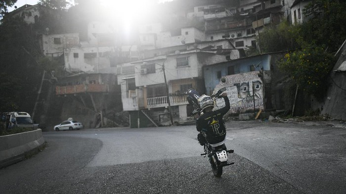 "Motorcycle stuntman Pedro Aldana performs a wheelie on his motorbike as he rides to an exhibition along the old highway from Caracas to La Guaira, Venezuela, Sunday, Jan. 10, 2021. Aldana, who prefers his show name ""Crazy Pedro, dares to beat the odds and put on exhibitions of speed and agility with a crew of like-minded daredevils atop their motorcycles. (AP Photo/Matias Delacroix)"