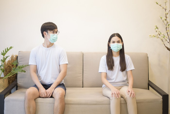 A couple wearing a mask is sitting on a sofa at home during quarantine for protection and avoiding from coronavirus
