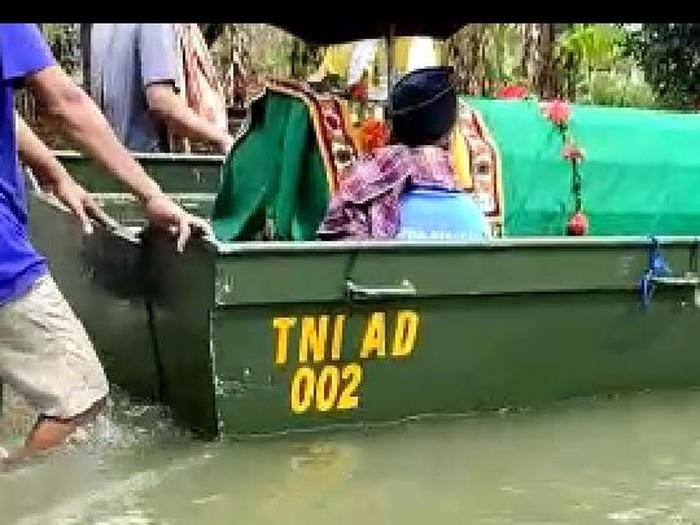 Jenazah seorang wanita warga Kudus dibawa pakai perahu menerobos banjir, Selasa (2/2/2021).
