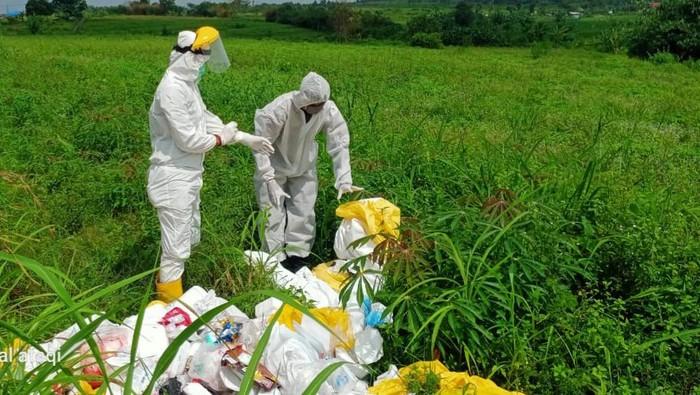 Petugas memeriksa belasan karung sampah medis yang dibuang di lahan kosong, Kabupaten Bogor.