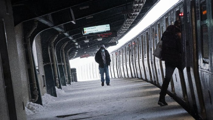 A man walks along a snow covered platform of a train station during a snowstorm, Monday, Feb. 1, 2021, in Brooklyn, New York. (AP Photo/Wong Maye-E)