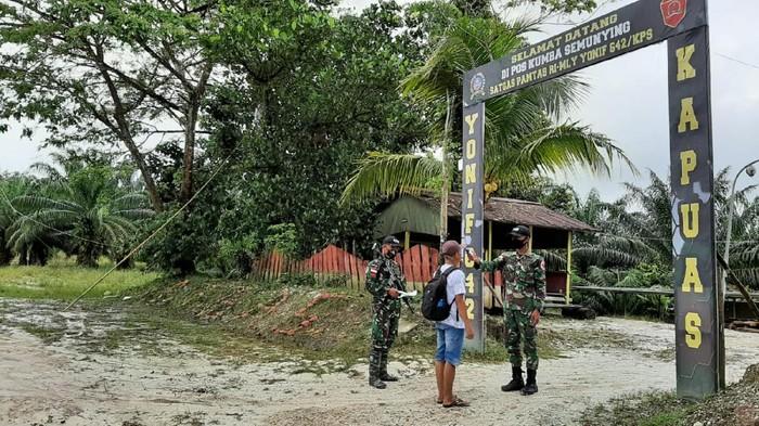 TNI bertugas di pos perbatasan Malaysia-RI. Mereka Menerapkan protokol kesehatran terhadap sispapun yang hendak memasuki RI