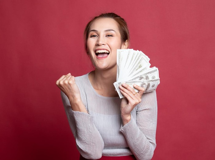 Portrait of  young asian woman  showing bunch of money banknotes on red background