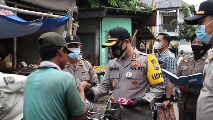 Operasi yustisi di Nganjuk juga diisi dengan pembagian masker. Pembagian masker dilakukan di tiga titik yang sering ditemukan pelanggan prokes.