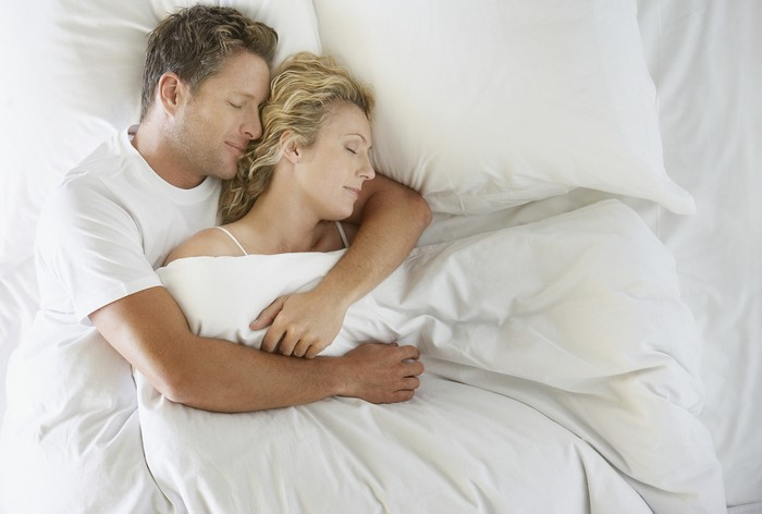 sleeping couple in bad hugging each other