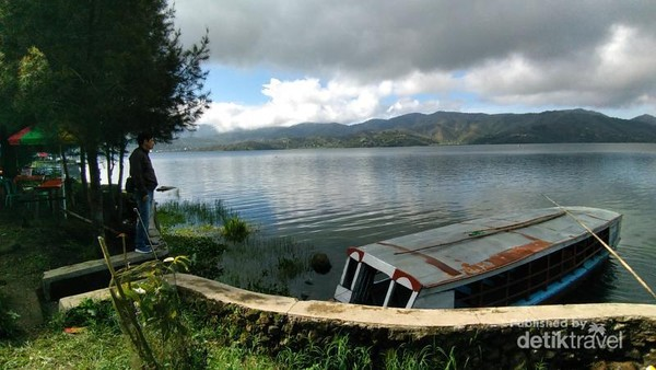 Sebuah perahu yang bersandar di dermaga danau yang tenang