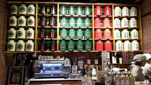 Berbagai jenis teh dalam kemasan kaleng besar tertata rapi di dinding