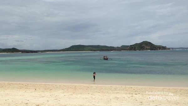 Paduan pasir putih dan biru kehijauan laut yang tenang