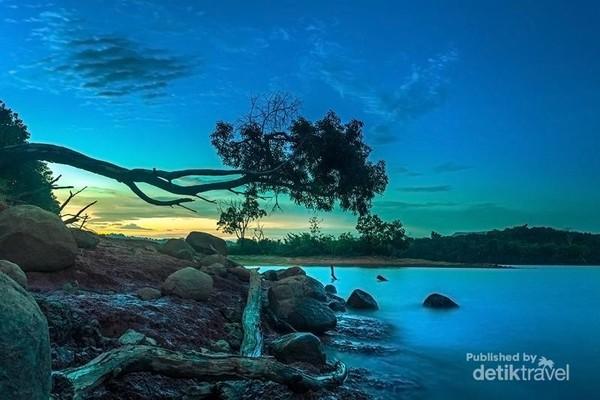 Pemandangan sejauh mata memandang adalah danau yang luas dan tenang, dengan latar perbukitan, warna langitnya juga luar biasa