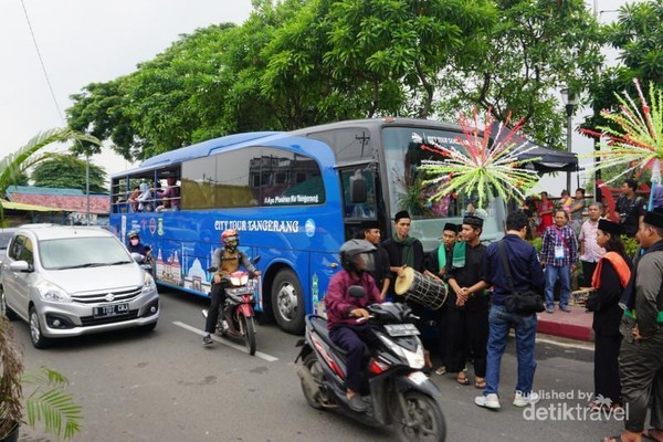 Bus berwarna biru dengan layout seat belakang menghadap ke depan