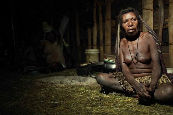 salah satu perempuan suku dani yang malam itu menyambut kami, tampak hanya mengenakan sali atau rok yang berumbai terbuat dari jerami